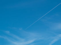Blue sky with vapour trail. A blue sky with a vapour trail running through the centre of the image with the aircraft being just a speck in the image Stock Photography