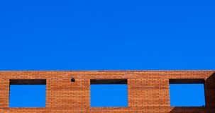 Blue sky visible through the window's holes frames in red brick wall. Building under construction stock photo