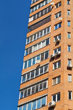 Blue sky and wall of multistorey house Stock Photography