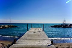 Blue sky and water with dock Royalty Free Stock Images