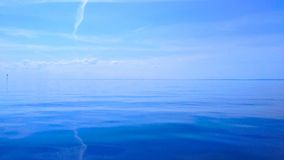 Blue sky and water. A magnificent horizon with clear blue sky and very still water Stock Photo