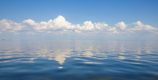 Blue sky, water and white clouds. The view of calm water and white clouds Stock Photo