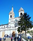 The Spanish steps in Rome on a sunny day. Blue sky and a white church at the Spanish steps in Rome, Italy Royalty Free Stock Photos