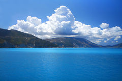 Blue sky white clouds. Blue sky and turquoise sea landscape with mountains and white clouds in horizon stock photos
