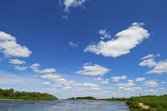 Blue sky,white clouds. Blue sky and white clouds are reflected in the river Stock Image