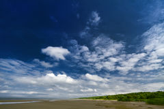 A blue sky with white clouds. Coastline Royalty Free Stock Photos