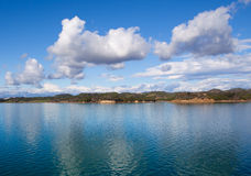 Blue sky and white clouds. With reflection in water Royalty Free Stock Images