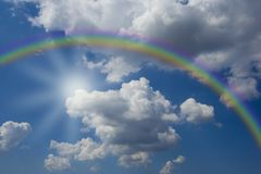 Blue sky with white clouds. And a beautiful raimbow royalty free stock image