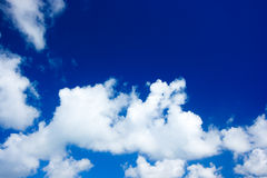 Blue sky and white clouds. Bright fluffy and cottony clouds against a dark blue sky royalty free stock photos