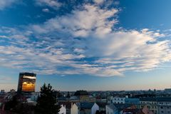 Blue sky with white clouds above city Zagreb, Croatia. Landscape view of Zagreb during sunset. Evening reflection in a building. Blue sky with white clouds Stock Images