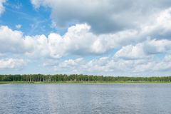 Blue sky with white clouds above the lake in the forest stock photos