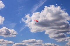 Blue Sky with White Clouds Background Parachuter. White puffy clouds against a bright blue sky with parachuter as a summer day background Royalty Free Stock Photography