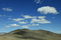 Blue sky with white clouds on bare mountain Royalty Free Stock Photography