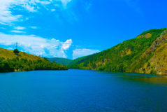Blue sky and white clouds. Big blue sky and some white clouds on a blue river and a forest Royalty Free Stock Photos