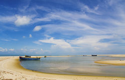 Blue sky, white clouds, boat on a sandbank, sea Royalty Free Stock Image
