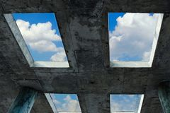 A blue sky with white clouds can be seen through the windows in a concrete building. The concept of faith, freedom and hope. Royalty Free Stock Photos