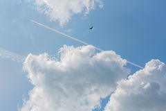 Blue sky with white clouds, contrails and black bird Stock Images