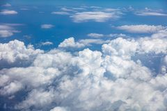 Blue sky, white clouds cover the earth background. Aerial photo from airplane`s window. Stock Image