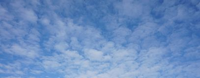 Blue sky with white clouds. Detail of blue sky with some white small  clouds for architectural, presentation backgrounds Royalty Free Stock Photo