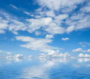 Blue sky and white clouds flaying over sea. Stock Photos