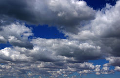 Blue sky with white clouds. White and gray fluffy clouds against the blue sky Royalty Free Stock Photo