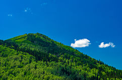 Blue sky, white clouds, green Altai Mountains at noon. Ridder, Kazakhstan Stock Photo