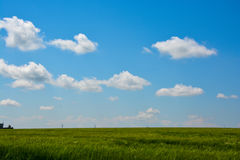 Blue sky with white clouds and green grass background on a summer day Stock Photos