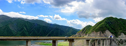 The blue sky, white clouds, green mountains and lake water, the cars driving out of the tunnel are speeding on the viaduct Royalty Free Stock Photos