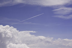 Blue sky, white clouds and jet condensation trail Royalty Free Stock Photos