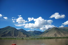Blue sky, white clouds, mountains, water. Royalty Free Stock Image