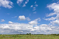 Blue sky with white clouds over a green field Royalty Free Stock Photography