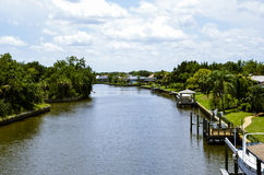 Blue sky with white clouds over inter-coastal with walkway to house Stock Photography