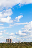 Blue sky with white clouds over urban buildings. And green forest in summer Royalty Free Stock Images
