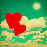 Blue sky with white clouds and red heart shaped balloons Royalty Free Stock Photography
