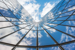 Blue sky and white clouds reflecting in a  glass building. Blue sky and white clouds reflecting in a curved glass building Stock Photos