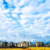 Blue sky with white clouds and residential buildings on the horizon royalty free stock images