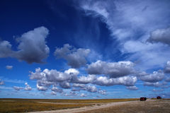 Blue sky with white clouds and road. Blue sky with white fluffy clouds and road across the steppe Stock Images