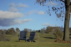 Two adirondek chairs waiting peacefully for their occupants on a late fall day in New England. Blue sky white clouds sile tree in forefront brown leaves field Stock Image