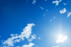 The blue sky with white clouds and the sun Stock Images