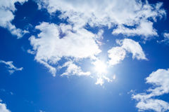 The blue sky with white clouds and the sun Royalty Free Stock Photo
