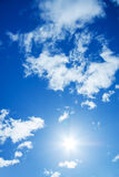 The blue sky with white clouds and the sun Stock Photo