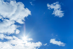 The blue sky with white clouds and the sun Stock Photography