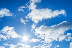 Blue sky with white clouds and the sun Stock Photos