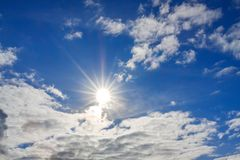 Blue sky with white clouds and sun. Background from blue sky with white clouds and sun. spring landscape with sunshine on heaven. moody sky Royalty Free Stock Photos