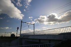 Blue sky with white clouds and sun beams at a railway bridge in Zevenhuizen Royalty Free Stock Image