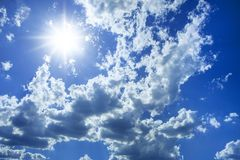 Blue sky, white clouds and sun. Clouds in the sky with sharp light-shadows. Sunny day stock photos