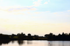Blue sky white clouds at sunset. Silhouette with water to the foreground , UK Royalty Free Stock Photos