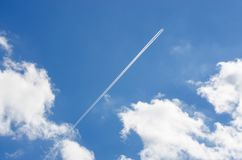 Blue sky. White clouds. Trace of the plane stock photography