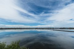 Blue sky and white clouds, water reflections in salt farming Na Stock Photo