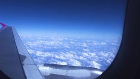 Blue sky, white clouds and wing view from window flying passenger airplane. Airplane wing on white clouds in blue sky stock video